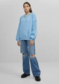 Bershka - MIT SCHLAGHOSE UND RISSEN - Jeans relaxed fit - dark blue - 1