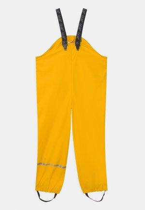 RAINWEAR OVERALL SOLID UNISEX - Spodnie przeciwdeszczowe - yellow