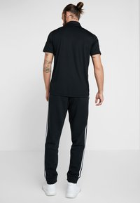 adidas Performance - Tracksuit bottoms - black/white - 2