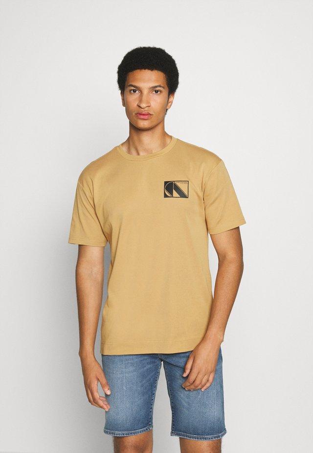 CLUB NOMADE TEE - Triko spotiskem - camel