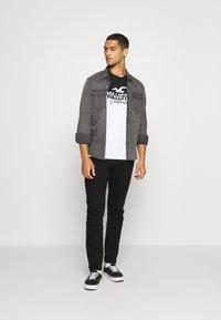 Hollister Co. - TECH LOGO SPLICING - Print T-shirt - black/white - 1