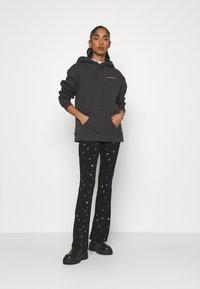 Colourful Rebel - STAR EYE PRINT BASIC FLARE PANTS - Trousers - black - 1