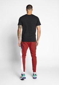 Nike Sportswear - Spodnie treningowe - university red/white - 2