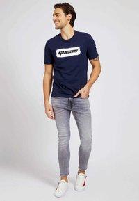 Guess - T-shirt con stampa - blau - 1