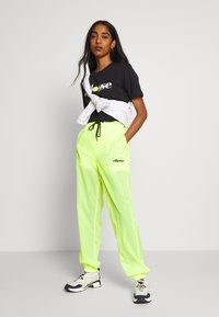 Ellesse - LA QUITANA X SMILEY - Tracksuit bottoms - neon yellow - 1
