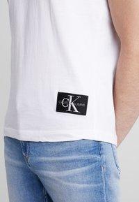 Calvin Klein Jeans - BADGE TURN UP SLEEVE - Basic T-shirt - bright white - 4