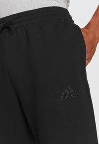 adidas Performance - ESSENTIALS - Tracksuit bottoms - black/white - 5