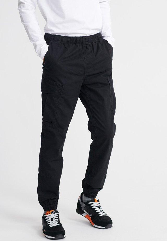 WORLDWIDE - Cargo trousers - black