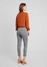 KIOMI - Trousers - black/white - 2