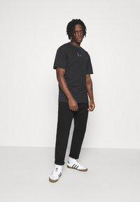 Karl Kani - SMALL SIGNATURE WASHED TEE UNISEX  - T-shirt med print - black - 1