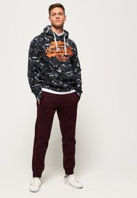 Superdry - LABEL CUFFED JOGGER - Tracksuit bottoms - bordeaux - 1