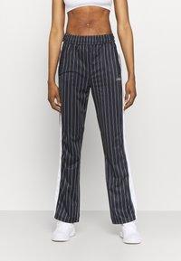 Fila - JAIMI PINSTRIPE TRACK PANTS - Teplákové kalhoty - black/bright white - 0