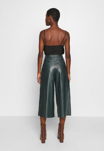 MEGHAN - Leather trousers - dark green