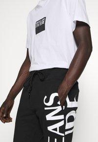 Versace Jeans Couture - BIG LOGO JOGGERS - Træningsbukser - black - 3