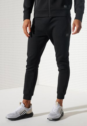 TRAINING GYMTECH - Tracksuit bottoms - black