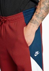 Nike Sportswear - Spodnie treningowe - university red/white - 5