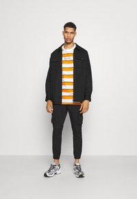 Karl Kani - SMALL SIGNATURE STRIPE TEE UNISEX - Print T-shirt - orange - 1