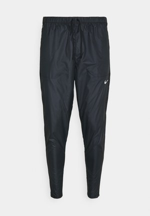 SHIELD - Tracksuit bottoms - black/reflective silver