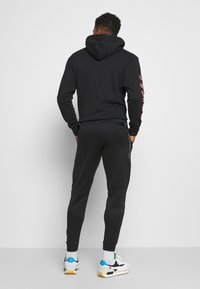 Nike Sportswear - TRIBUTE - Tracksuit bottoms - black/white - 2