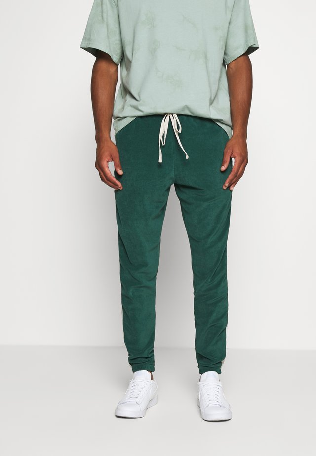 TRACKPANTS LOUNGIN - Tracksuit bottoms - green/off white