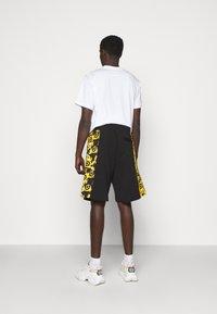 Versace Jeans Couture - PRINT LOGO BAROQUE - Tracksuit bottoms - black - 2