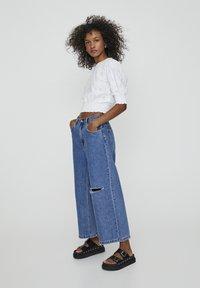 PULL&BEAR - MIT ZIERRISSEN - Flared Jeans - dark blue - 1