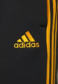 adidas Performance - 3 STRIPES  ESSENTIALS - Tracksuit bottoms - black/semi solar gold - 5