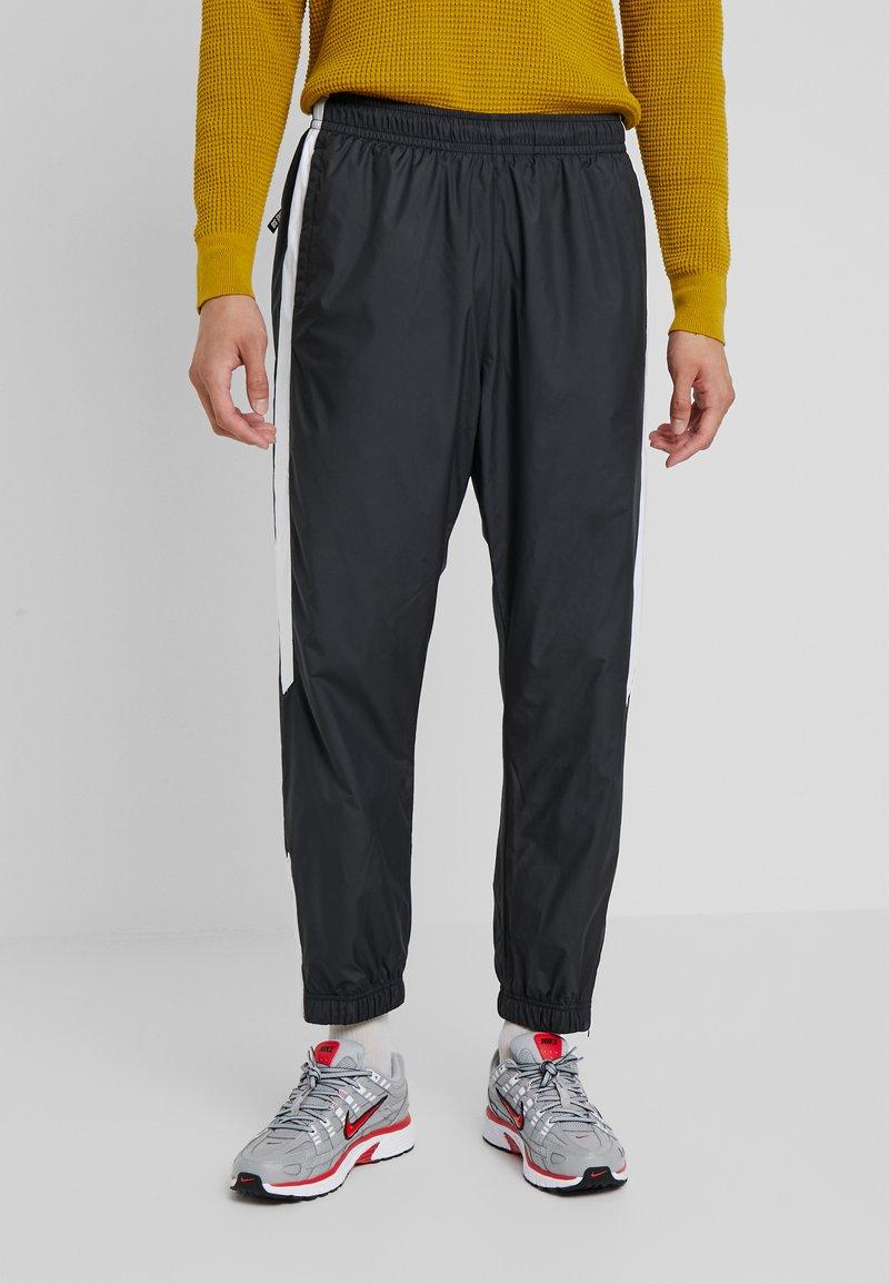 Nike SB - SHIELD - Tracksuit bottoms - black/white