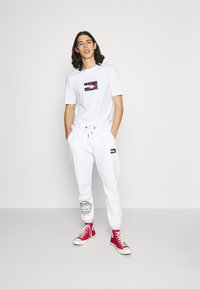 Tommy Hilfiger - ONE PLANET UNISEX - Tracksuit bottoms - white - 1