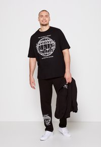 Tommy Hilfiger - ONE PLANET FRONT LOGO TEE UNISEX - Print T-shirt - black - 3