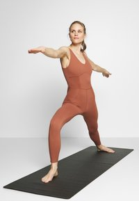 Nike Performance - W NK YOGA LUXE JUMPSUIT - Turnanzug - red bark/terra blush - 1