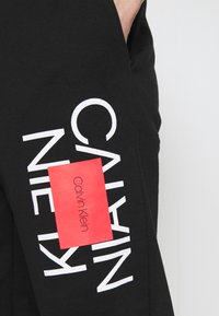Calvin Klein - TEXT REVERSED  - Tracksuit bottoms - black - 5