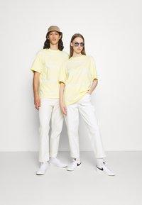 Karl Kani - SIGNATURE TIE DYE TEE UNISEX - T-shirt imprimé - light yellow - 1