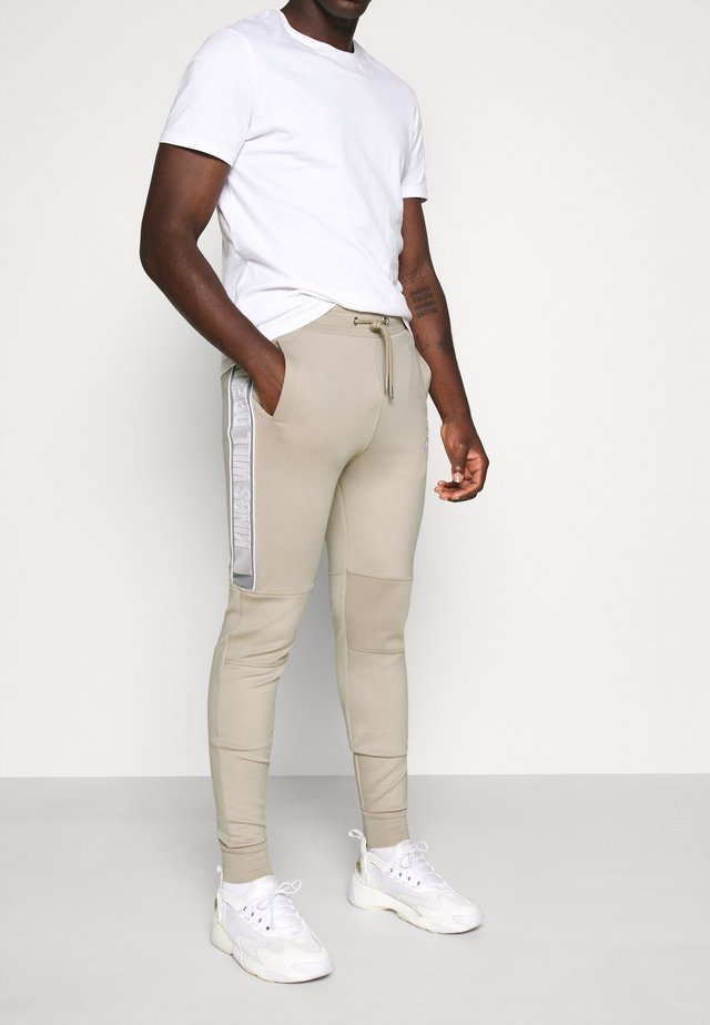RALLOR JOGGERS - Tracksuit bottoms - sand