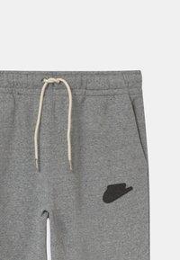 Nike Sportswear - REGRIND UNISEX - Tracksuit bottoms - black/dark smoke grey - 2