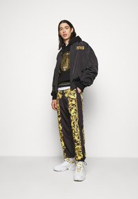 Versace Jeans Couture - PRINT BAROQUE - Tracksuit bottoms - black - 1