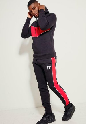 Pantalones deportivos - black/goji berry red