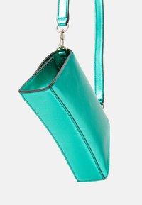 Guess - DEVIN CROSSBODY WRISTLET - Handbag - green - 3