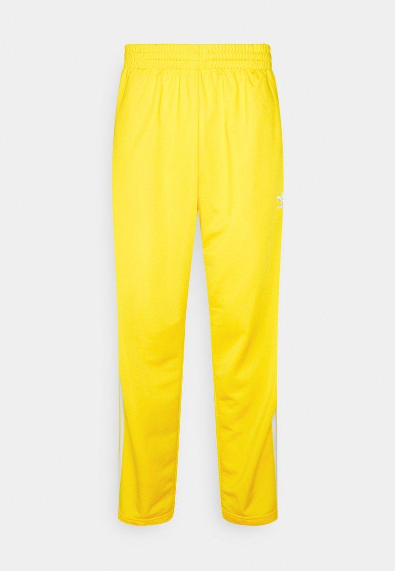 adidas Originals - FIREBIRD UNISEX - Tracksuit bottoms - yellow
