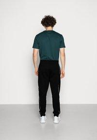 Calvin Klein - LOGO PRINT - Spodnie treningowe - perfect black - 2