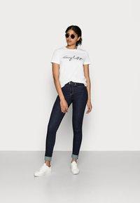 Tommy Hilfiger - HERITAGE CREW NECK GRAPHIC TEE - T-shirt z nadrukiem - classic white - 1