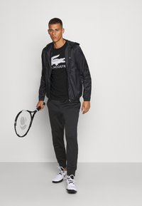 Lacoste Sport - TENNIS PANT - Tracksuit bottoms - black - 1