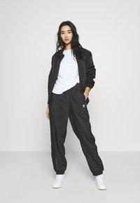 adidas Originals - BELLISTA NYLON CUFFED SPORT PANTS - Verryttelyhousut - black - 1