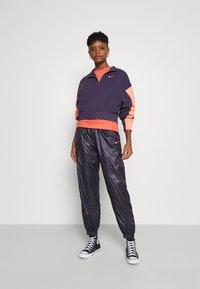 Nike Sportswear - Tracksuit bottoms - dark raisin/bright mango - 1