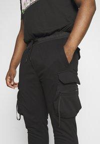 Urban Classics - TACTICAL PANTS - Tracksuit bottoms - black - 4