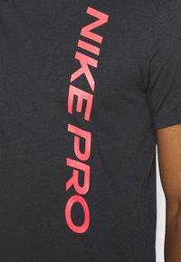 Nike Performance - BURNOUT - Print T-shirt - black/bright crimson - 3