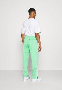 adidas Originals - FIREBIRD UNISEX - Spodnie treningowe - semi screaming green - 2