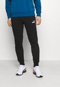 Puma - AMPLIFIED PANTS - Pantalon de survêtement - black - 0