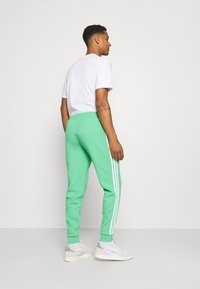 adidas Originals - 3 STRIPES PANT - Tracksuit bottoms - semi screaming green - 2