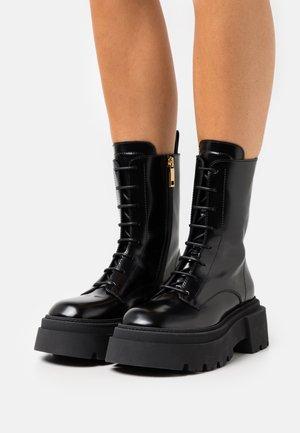 OSCURI BOOT - Platform ankle boots - black